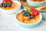 Vanilla Bean Creme Brulee in three ramekins with berries.