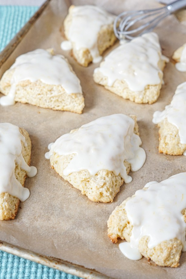 Meyer Lemon Scones on a parchment-lined baking sheet next to a whisk.
