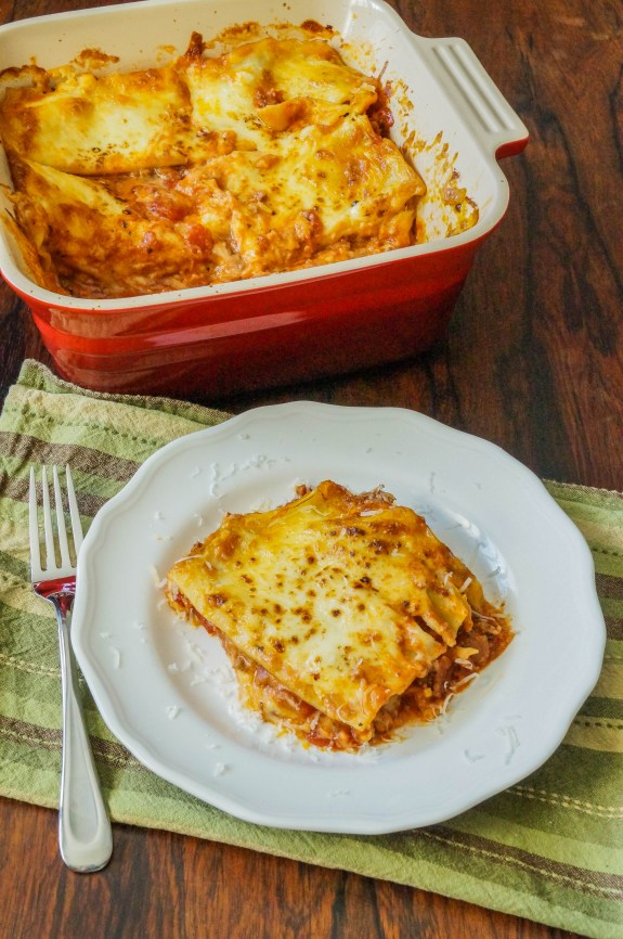 Pasticho (Venezuelan Lasagna) in a red pan with a slice on a white plate