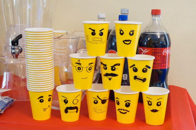 Yellow paper cups decorated with lego faces.