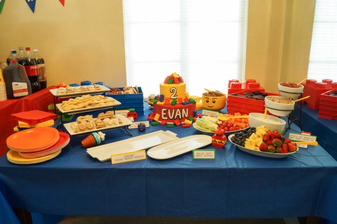 Blue table topped with white platters of food and two tier lego birthday cake.