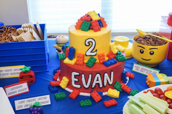 Red and yellow lego birthday cake with Evan on first tier and 2 on second tier.