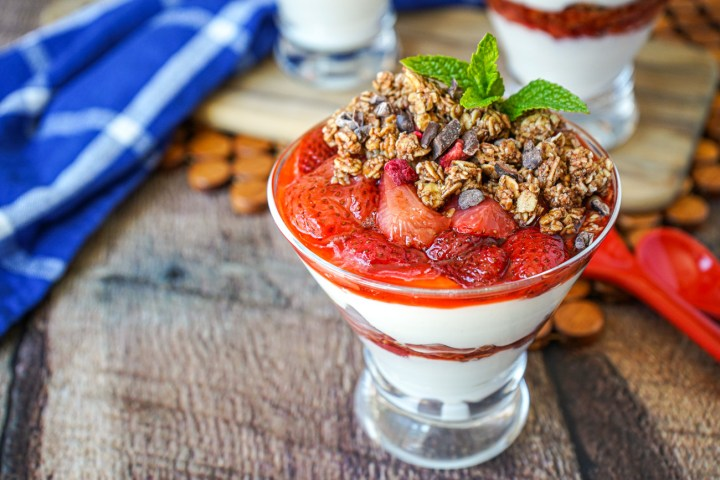 Close up of Roasted Strawberry Parfaits in clear glass cups with granola and mint.