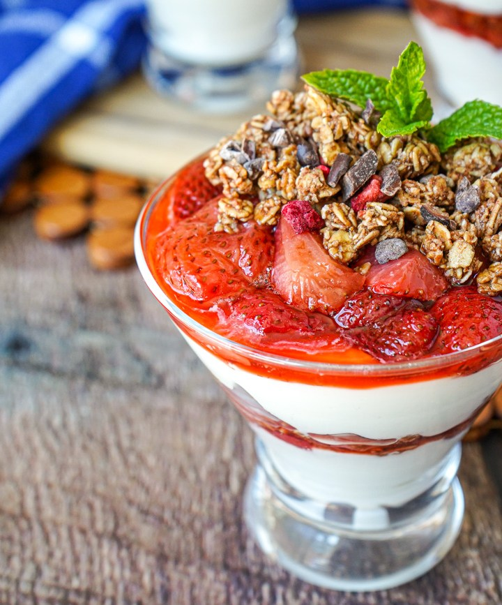 Roasted Strawberry Parfaits in clear glasses and topped with mint.