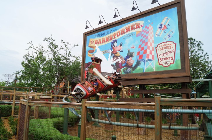 Riding the Barnstormer at Disney World Magic Kingdom- small roller coaster shaped like a red plane with a billboard in the background of Goofy- The Barnstormer, Stupendous Stunts.