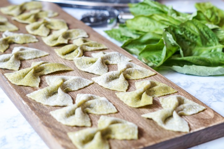 Side view of Homemade Basil Farfalle arranged in a single layer on a wooden board.