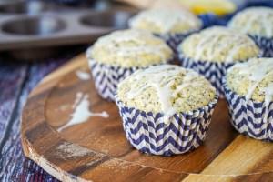 Lemon Poppy Seed Muffins with a lemon glaze on a wooden board.