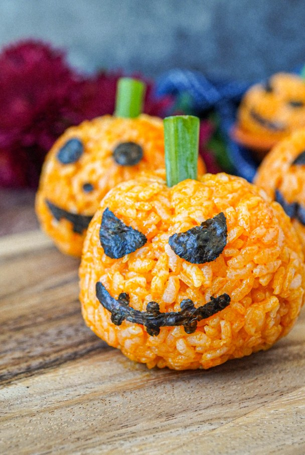Close up of Jack-O-Lantern Carrot Rice with nori face and green onion stem.