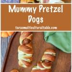 Mummy Pretzel Dogs on a wooden board next to pumpkins.