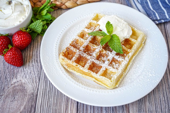 Gaufre de Bruxelles (Brussels Waffle) on a white plate with powdered sugar, fresh mint, and whipped cream.