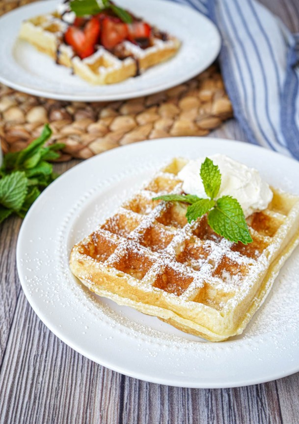 Close up of Gaufre de Bruxelles (Brussels Waffle) on two white plates with mint.