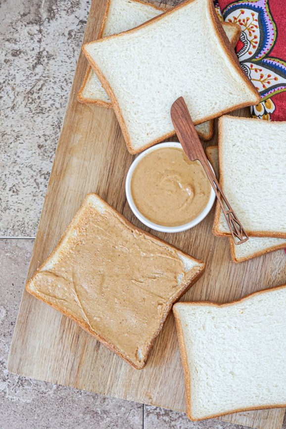Spreading peanut butter over a slice of bread next to 5 more slices of bread and peanut butter in a white bowl with a wooden knife.