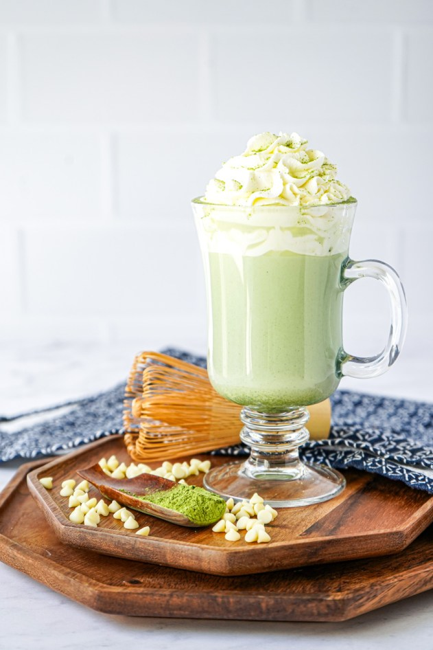 Side view of Matcha Hot Chocolate in a tall clear glass on two wooden boards.