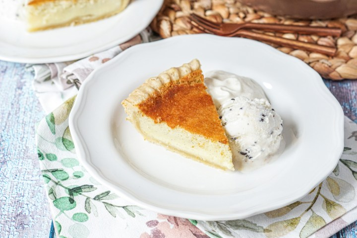 Close up of a slice of Vanilla Bean Buttermilk Pie on a white plate with ice cream and whipped cream.