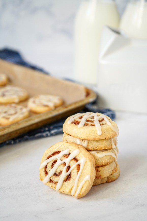 Side view of stacked Cinnamon Roll Cookies with milk containers in the background.