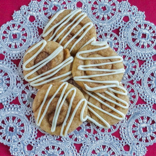 Aerial view of five Cinnamon Roll Cookies topped with a white chocolate drizzle.