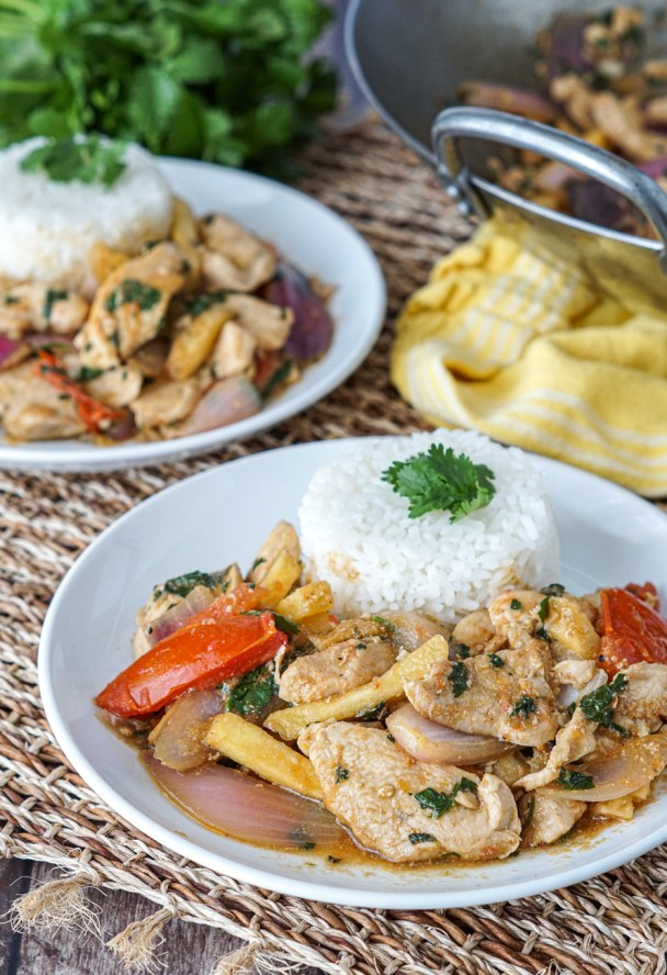 Pollo Saltado (Peruvian Chicken Stir-Fry) on two white plates with wok in background.