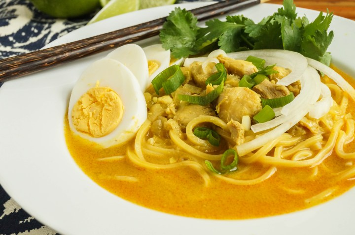 Close up of Ohn No Khauk Swe (Burmese Chicken Coconut Noodle Soup) with hard boiled eggs.