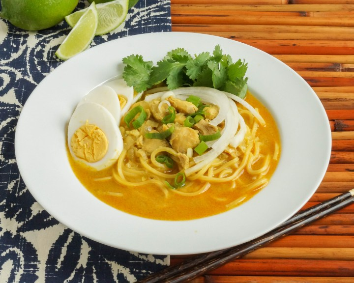 Ohn No Khauk Swe (Burmese Chicken Coconut Noodle Soup) in a white bowl next to lime wedges.