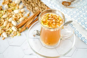 Aynar (Lebanese Spiced Tea) in a clear glass with chopped nuts.