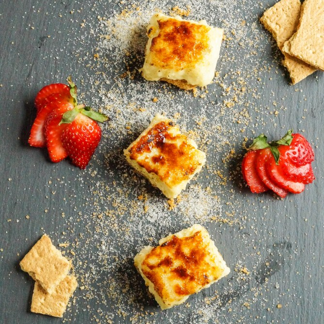 Aerial view of three Creme Brulee Cheesecake Bars on a board next to sliced strawberries and graham crackers.