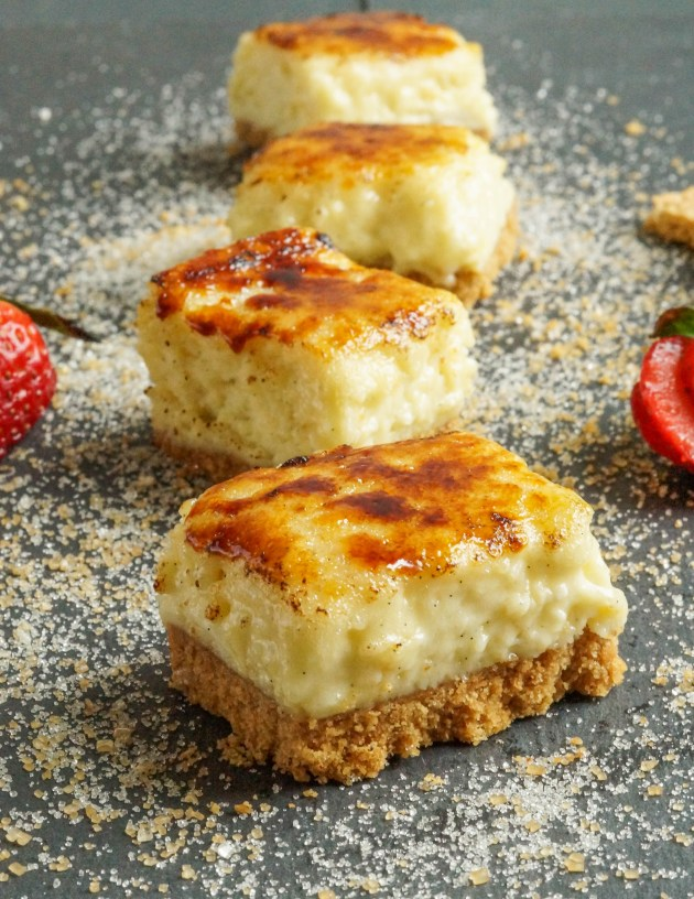 Four Creme Brulee Cheesecake Bars arranged in a line with a sprinkling of sugar.