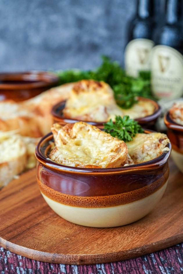 Side view of Guinness Onion Soup in three brown bowls with Guinness bottles in the background.