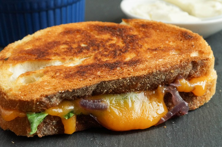 Grilled Cheese with Caramelized Onions and Spinach with mayonnaise in background.