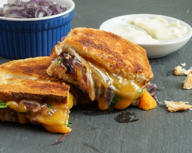 Grilled Cheese with Caramelized Onions and Spinach cut in half.