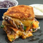 Two stacked slices of Grilled Cheese with Caramelized Onions and Spinach.