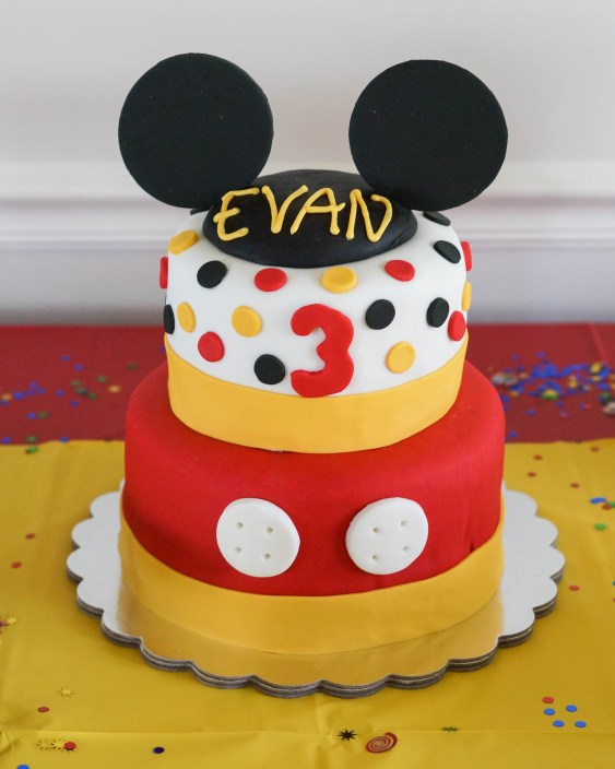 Mickey Mouse Birthday Cake with two tiers and black ears on top.