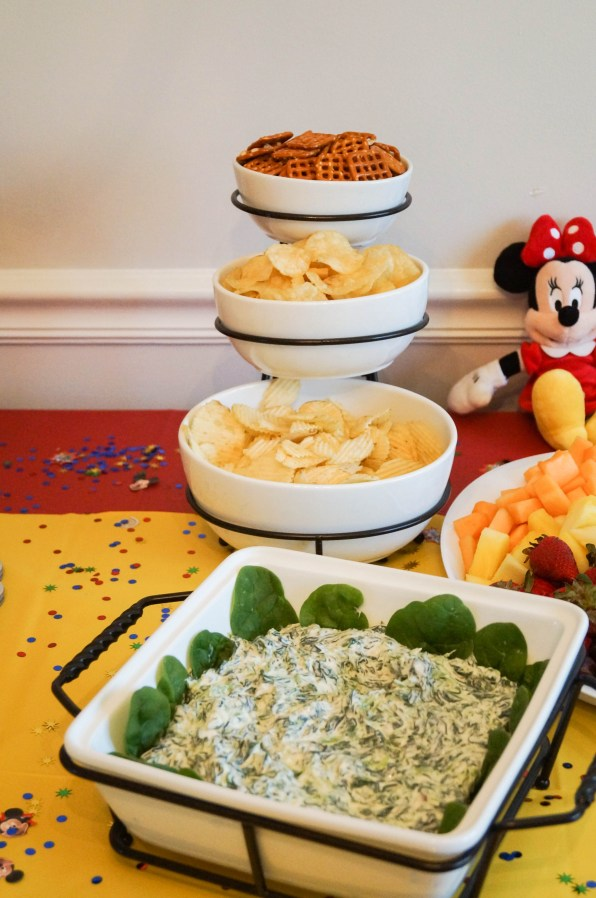 Chips, pretzels, and spinach dip in white bowls.