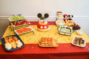 Food on red and yellow table with Mickey Mouse cake.