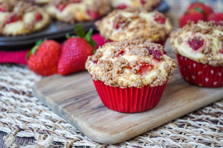 Three Strawberry Cheesecake Muffins in red liners on a wooden board.