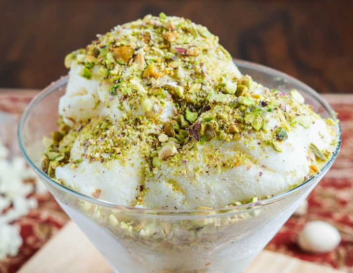 Close up of Éma'a (Syrian Ice Cream) in a glass bowl and covered with crushed pistachios.
