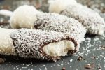 Three Esquimos (Coconut Sorbet Ice Pops Dipped in Chocolate and Coconut) on a board and covered in coconut flakes.