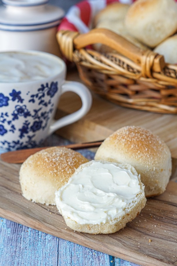Pandesal (Filipino Bread Rolls) split in half and served with butter. Coffee and more rolls in the background.
