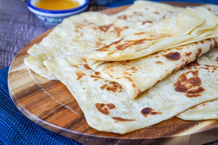 Msemen (Moroccan Square Flatbread) piled on a wooden board.