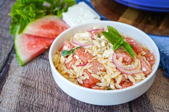 Watermelon Feta Orzo Salad in a white bowl next to slices of watermelon, feta, and fresh mint.