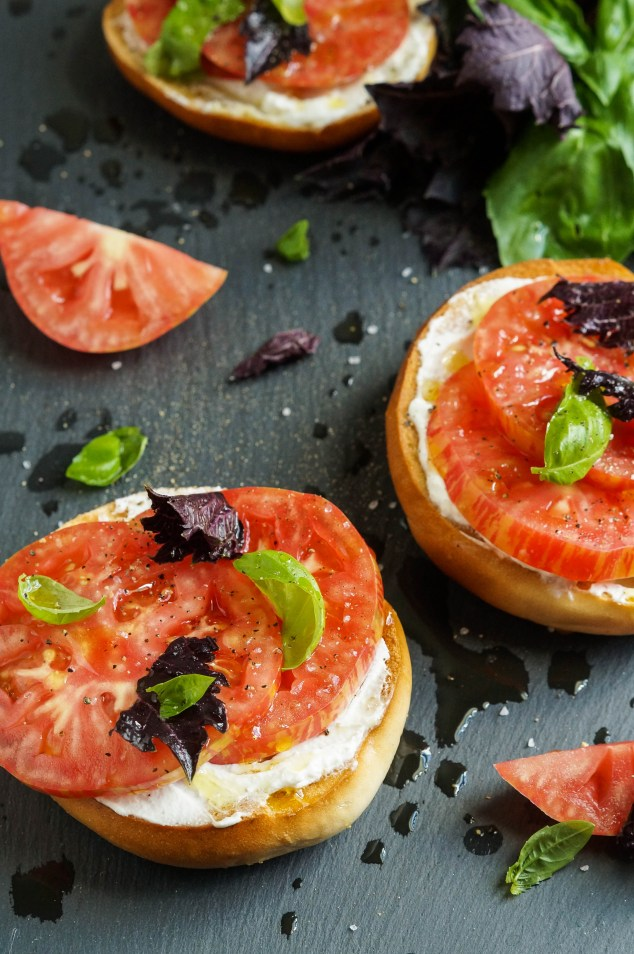 Aerial view of Crisp Toasted Bagels with Fromage Blanc, Tomato, Sea Salt, and Basil with scattered tomatoes and basil leaves.
