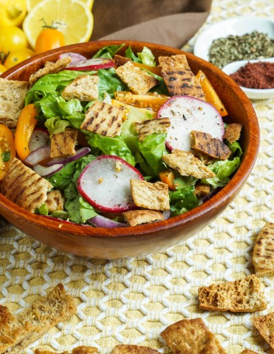 Fattoush in a wooden bowl on a yellow placemat