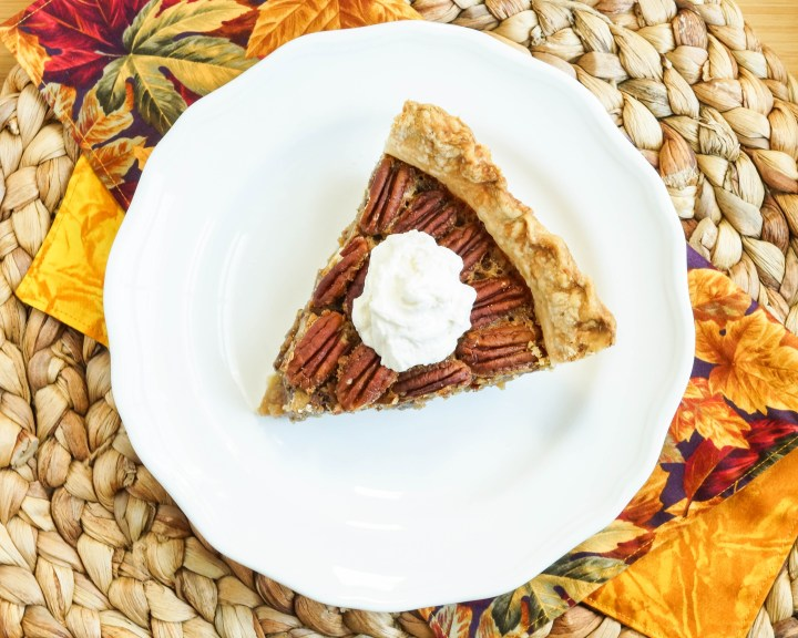 Aerial view of a slice of Pecan Pie on a white plate and topped with a dollop of whipped cream.