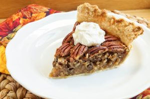 A slice of pecan pie on a white plate with a dollop of whipped cream.