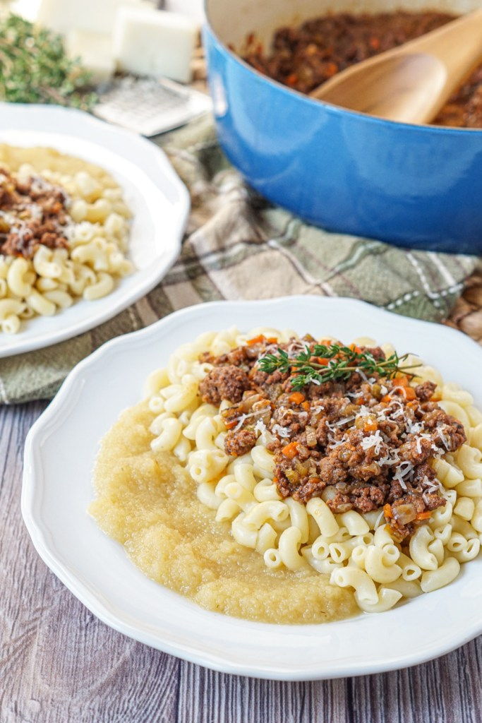 Close up of Ghackets mit Hörnli (Swiss Macaroni with Meat Sauce) on a white plate with a blue pot in the background with a wooden spoon and more meat sauce.