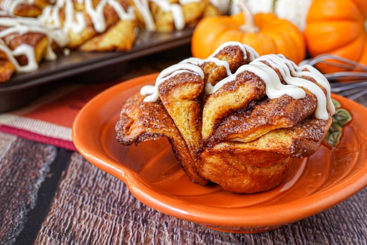 Pumpkin Cinnamon Fantail Rolls on a pumpkin plate and in a muffin tin.