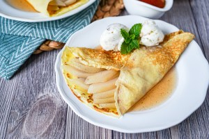 Champagne Poached Pear Crepes on a white plate with two scoops of ice cream.