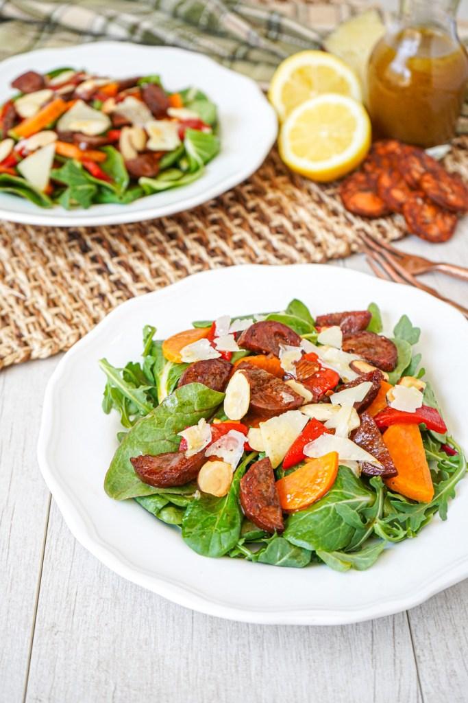Chorizo and Sweet Potato Salad on two white plates next to chorizo slices, lemon, and vinaigrette.