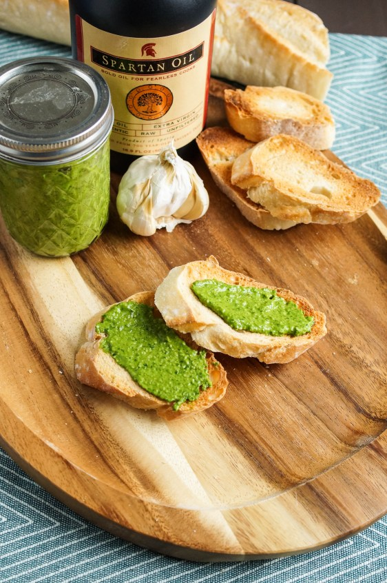 Spinach Walnut Pesto in a jar and spread over two slices of toasted baguette with garlic, baguette, and olive oil jar in background.