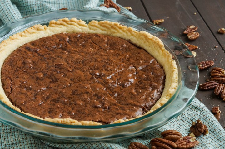 Brownie Pecan Pie in a clear glass pie dish.