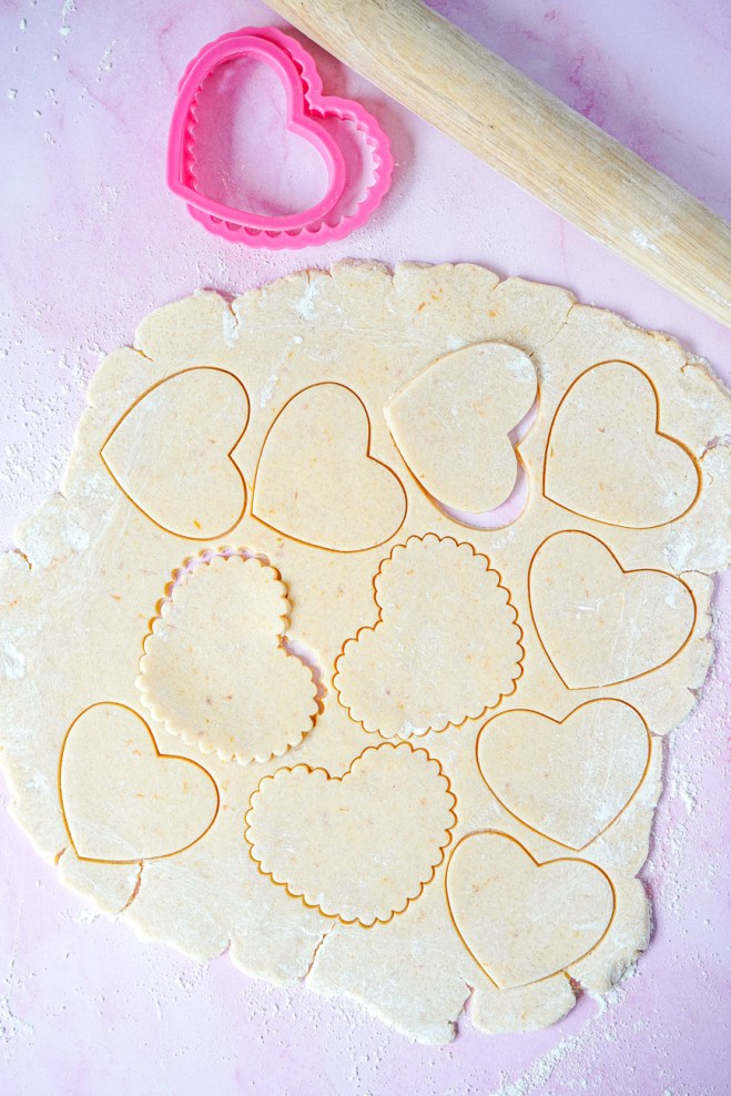 Aerial view of the raw Blood Orange Shortbread Cookie dough rolled into a sheet and cut into hearts.
